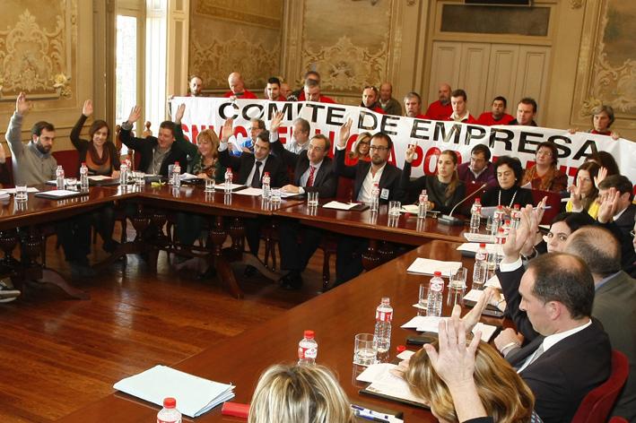 Miembros del comité de empresa portan una pancarta durante la celebración del pleno.